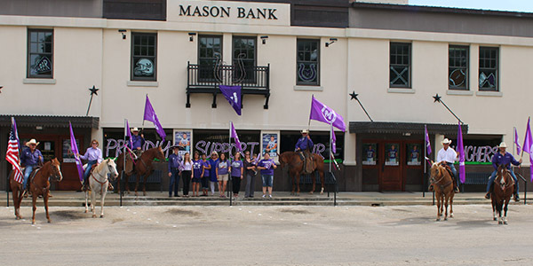 Mason Bank group photo with cowboys on horse and flags